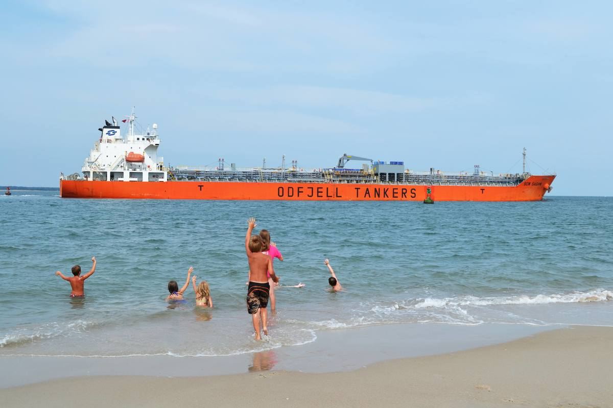 Children wave at an Odfjell chemical tanker in Moorehead, US. Photo by Charles Leeuwenburg